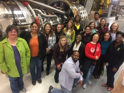 17 individuals stand near an aircraft engine and the GE Aviation plant